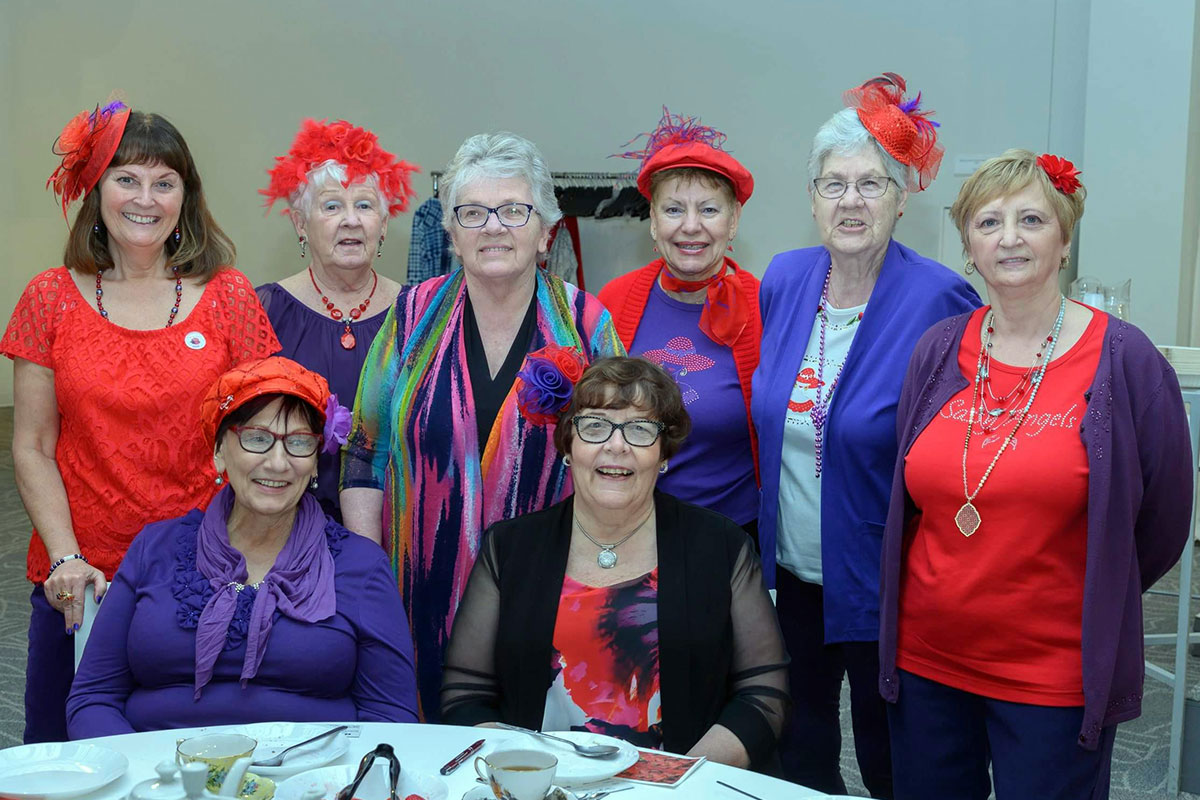 A group of ladies called, Red Hat Ladies, at the Strawberry Social looking very fasionable